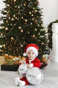 Un petit enfant dans un costume de père noël posant avec des boules disco dans un intérieur décoré pour le nouvel an