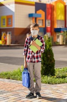 Un petit enfant dans un masque avec un sac d'école lors d'une épidémie de virus près du mur de l'école