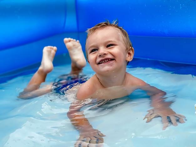 Un petit enfant dans une piscine ronde gonflable pour enfants par temps ensoleillé d'été. concept d'été et de vacances.