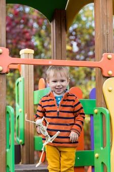 Un petit enfant dans un pull rayé tient un jouet squelette dans ses mains et descend un toboggan sur l'aire de jeux