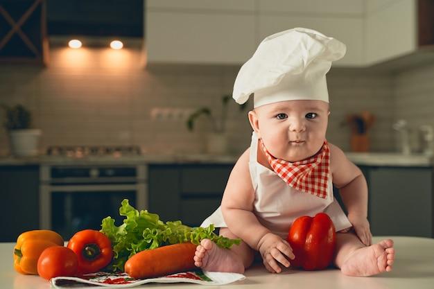 Un petit enfant dans une toque est assis à côté de légumes