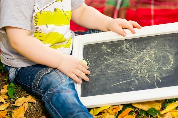 Petit enfant dessine à la craie