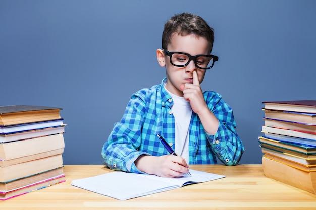 Petit enfant écrit dans le cahier et choisit son nez, concept de devoirs d'école. jeune élève au bureau en classe