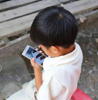 Petit enfant enfant garçon jouant un téléphone mobile intelligent