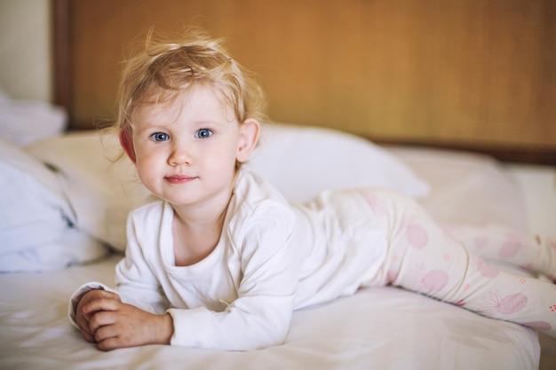 Petit enfant est allongé dans la chambre sur le lit et souriant dans mon pyjama
