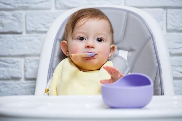 Un petit enfant est assis sur une chaise haute et mange de la nourriture dans une assiette avec une cuillère. ustensiles en silicone pour bébé pour nourrir les bébés