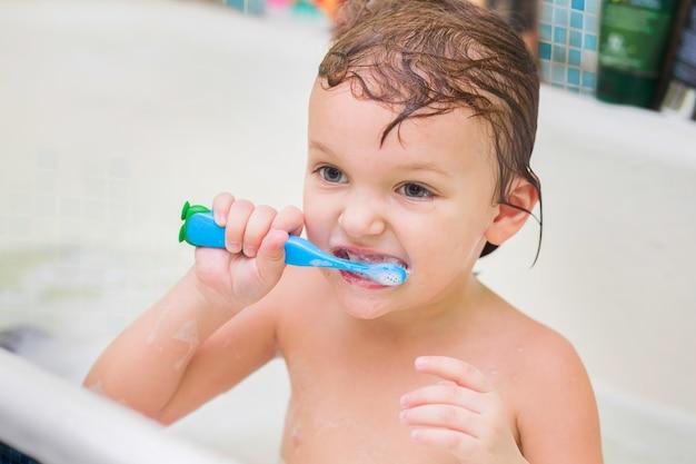 Le petit enfant est assis dans la salle de bain et se brosse une brosse bleue aux dents