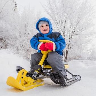 Un petit enfant est assis sur une scooter des neiges en hiver