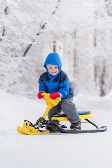 Un petit enfant est assis sur un scooter des neiges en hiver