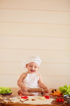 Le petit enfant est assis sur la table près de la pâte et des légumes