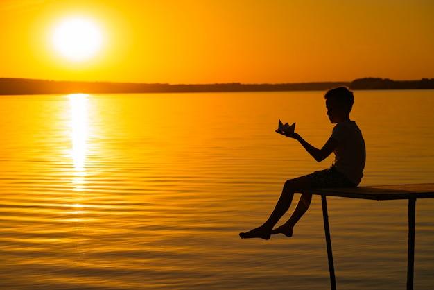 Un petit enfant est sur un pont avec un origami en forme de bateau dans ses mains au coucher du soleil. les jambes de l'enfant descendent dans l'eau qui s'écoule sous le pont
