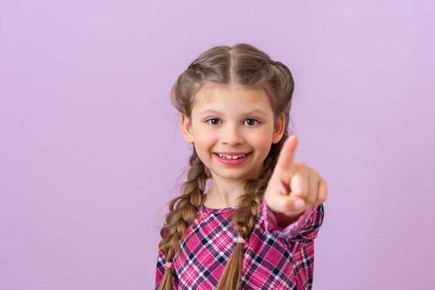 Le petit enfant est très heureux et pointe le doigt vers l'avant sur fond violet clair