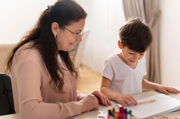 Petit-enfant à faire ses devoirs avec grand-mère