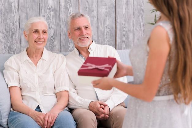 Un petit-enfant fait un cadeau à ses grands-parents