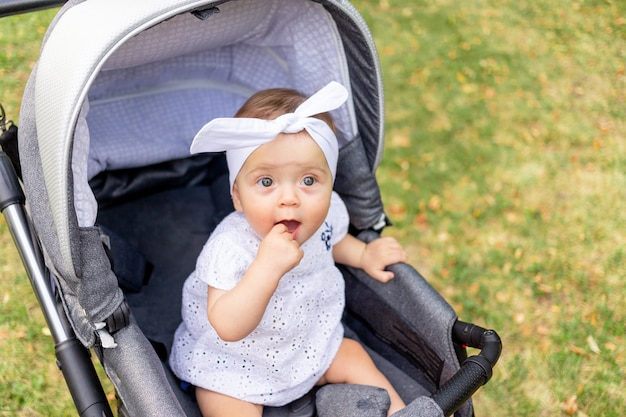 Un petit enfant une fille de 7 mois est assis dans une poussette en été dans une robe blanche et regarde la caméra
