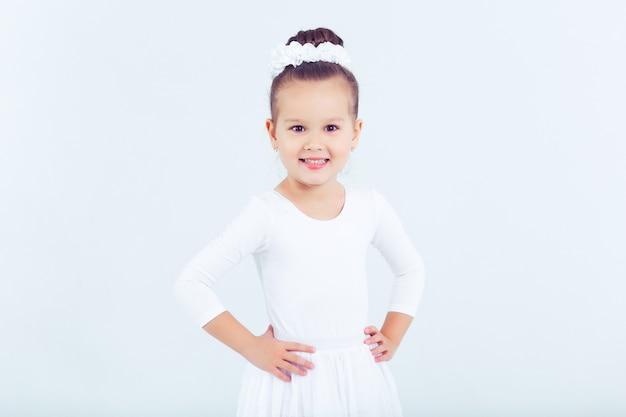 Petit enfant fille ballet de danse à fond blanc portrait de petite ballerine souriant