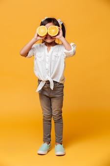 Petit enfant fille couvrant les yeux avec orange.