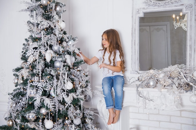 Petit enfant fille décorer un arbre de noël en intérieur classique blanc, assis sur une cheminée avec miroir. joyeux noël, bonne année, joyeuses fêtes.