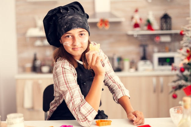 Petit-enfant gai le jour de noël tenant une pâtisserie en forme de coeur
