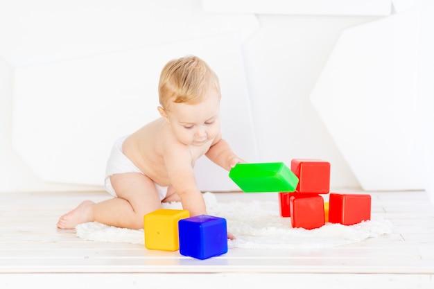 Un petit enfant un garçon de six mois joue avec des cubes lumineux dans une pièce blanche lumineuse en couches