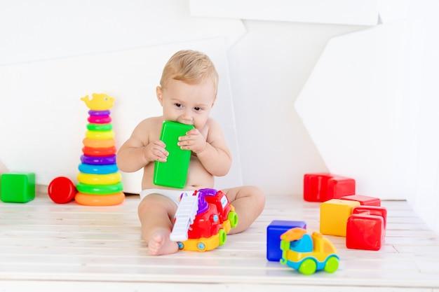 Un petit enfant un garçon de six mois joue avec des jouets lumineux dans une pièce blanche lumineuse dans les couches et les grignote