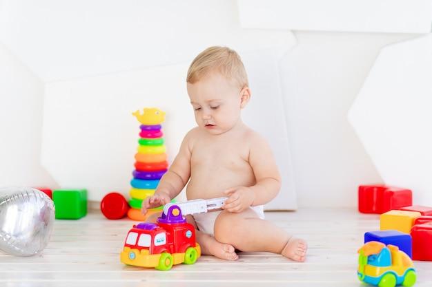 Un petit enfant un garçon de six mois joue avec des jouets lumineux dans une salle blanche et lumineuse en couches