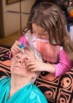 Petit-enfant gouttes pour les yeux à la grand-mère à la maison