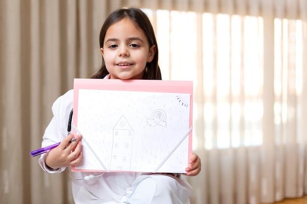 Petit enfant habillé en médecin montrant un dessin qu'elle vient de faire