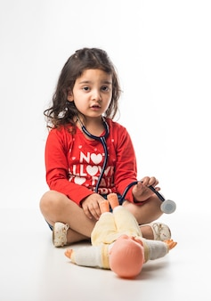 Petit enfant indien fille avec stéthoscope et peluche bébé ou chiot toy sitting against white background