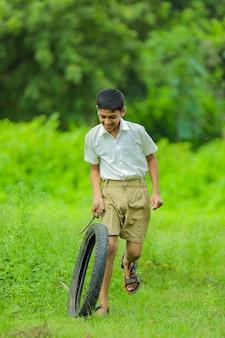 Petit enfant indien jouant avec des pneus au champ