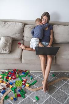 Un petit enfant joue sur le canapé pendant que maman travaille avec un ordinateur portable, distrait et interfère avec le travail de maman