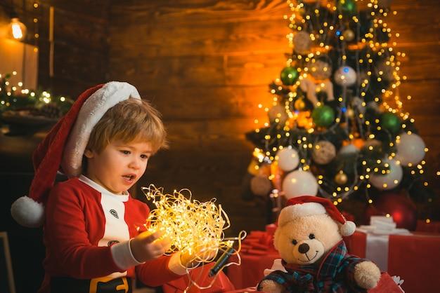 Petit enfant joue avec la lumière de noël sur fond d'arbre de noël