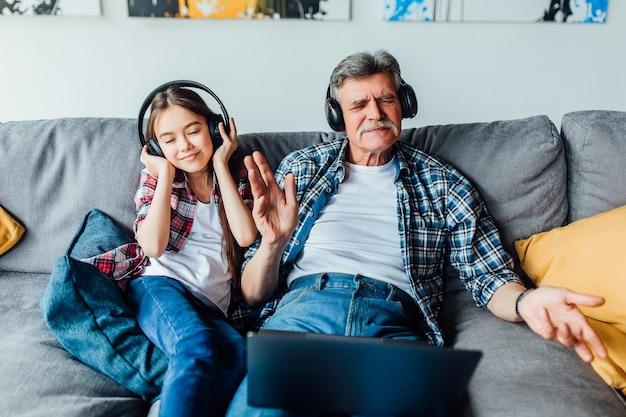 Petit-enfant joyeux et son grand-père écoutant de la musique sur une tablette numérique tout en étant assis sur un canapé.