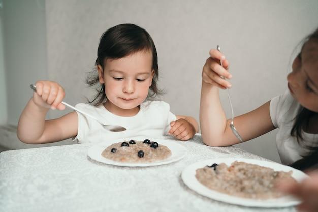 Un petit enfant mange des flocons d'avoine avec des baies. la fille tient une cuillère dans ses mains
