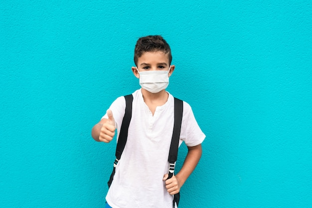 Petit enfant avec masque de retour à l'école avec les pouces vers le haut