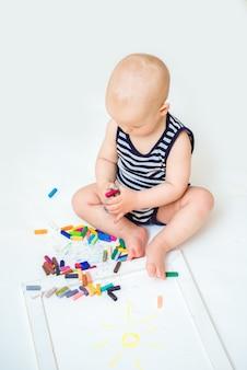 Petit enfant mignon avec créativité dessine avec des crayons à la maison sur une feuille de papier blanc. le concept du développement précoce de la créativité chez les enfants