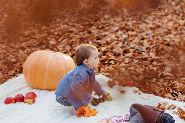 Petit enfant mignon dans le parc sur une feuille jaune avec citrouille en automne