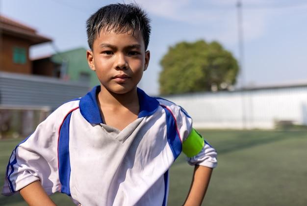 Un petit enfant mignon rêve de devenir joueur de football. concept de sport et d & # 39; activité