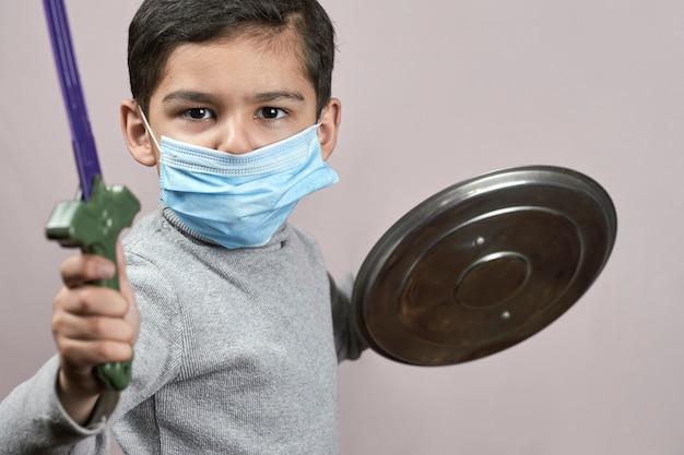 Petit enfant moddle-oriental dans un masque facial s'amusant pendant la quarantaine covid-19