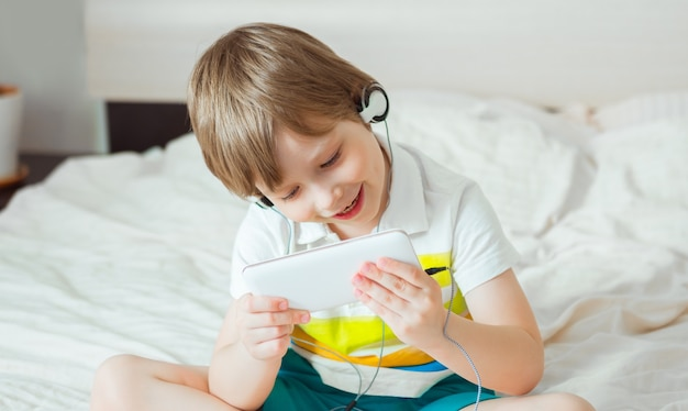 Petit Enfant Moderne Assis Sur Le Lit Avec Smartphone Dans Ses Mains Photo Premium