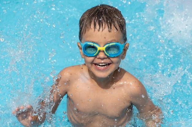 Un petit enfant nage dans la piscine, joue aux éclaboussures d'eau