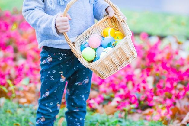 Petit enfant avec des oeufs de pâques en busket sur pâques en plein air