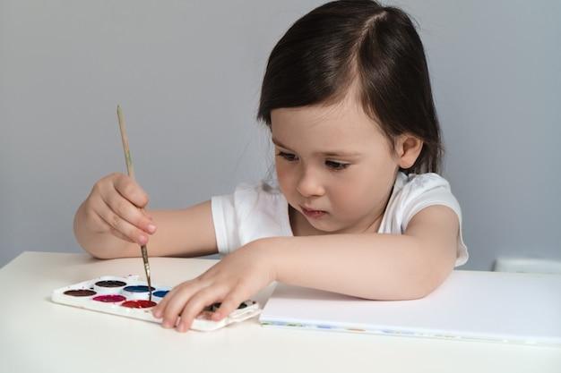 Un petit enfant peint une image à l'aquarelle. compétences en dessin créatif chez les enfants