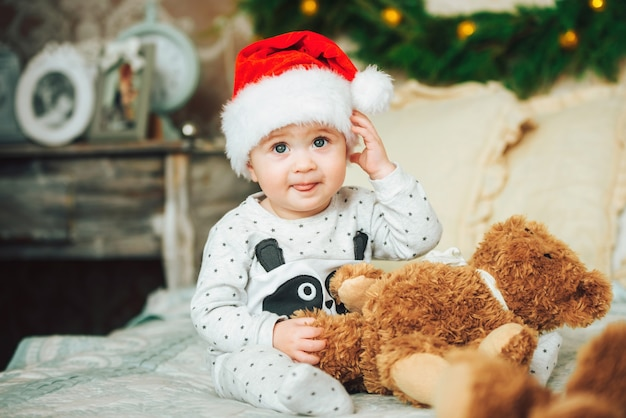 Petit enfant portant une casquette de noël rouge montre de manière amusante la langue