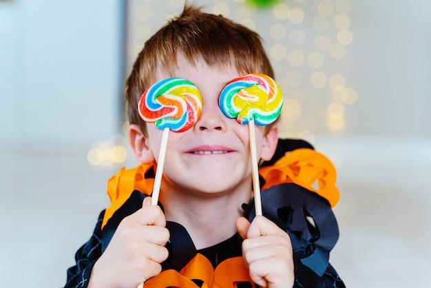 Petit enfant de race blanche jouant avec des bonbons de trucs ou de friandises recueillis à la fête costumée d'halloween