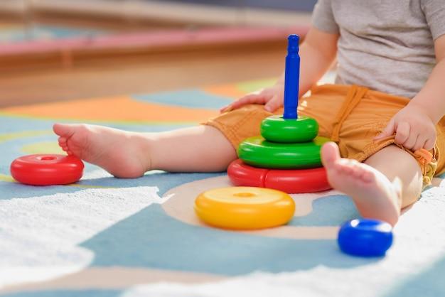 Le petit enfant ramasse une piraimda assise sur un sol