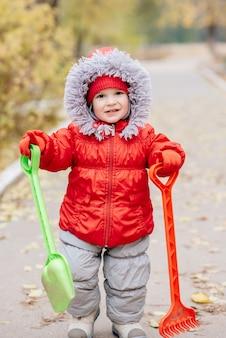 Un petit enfant avec un râteau et une pelle se promène dans le parc