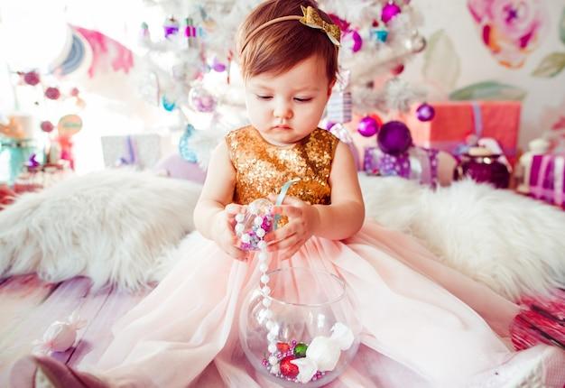 Petit enfant en robe dorée joue sur le sol