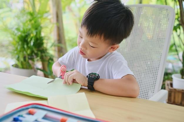 Petit enfant s'amusant à faire de l'art et de l'artisanat à la maison jardin arrière-cour sur la nature childrens art project