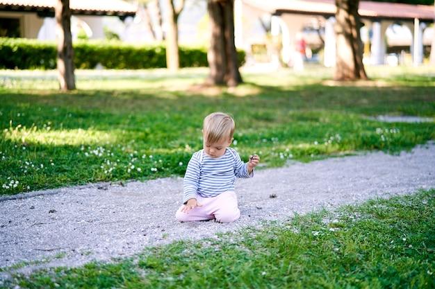 Le petit enfant s'assied sur ses genoux sur une passerelle au milieu d'une pelouse verte